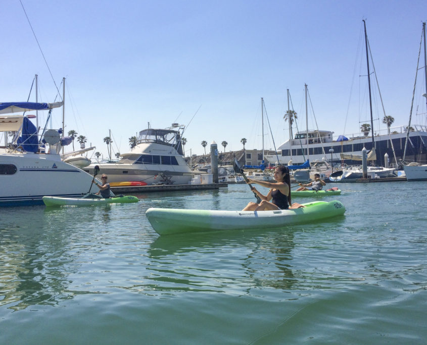 Girl having fun kayaking thru channel islands harbor on a beautiful sunny day.